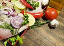 Meat raw chicken leg still life, greens, red pepper uncooked , dish table tomato, lemon garlic, pomegranate nutrition Royalty Free Stock Photos