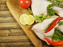 Meat raw chicken leg greens lemon, red chili pepper, nutrition tomato Royalty Free Stock Images