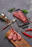 Meat Raw Fresh Mutton on the bone Spices Chesno and Rosemary on a black background royalty free stock image