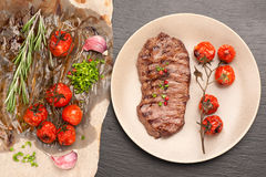 Meat Ribeye steak entrecote with roasted tomatoes and herbs Royalty Free Stock Photo