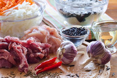 Meat, rice, garlic and other spices. On the kitchen table Stock Photos