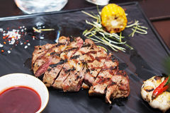 Meat roasted on skewers. Barbeque meat composition on a black background with tomato sauce, corn, rosemary and pepper. Appetizing meat roasted BBQ grill Stock Photos