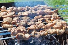 Meat is roasted on skewers in smoke. Shashlyk grilled on metal skewers  with smoke Royalty Free Stock Photos