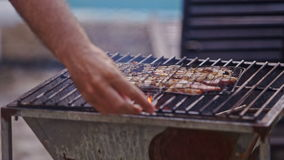 Meat roasts on fire on barbecue grid guy blows. Meat roasts on fire on metal barbecue grid above open flame guy blows to flame in day light background stock video footage