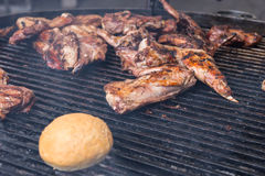 Meat and a roll grilling on a BBQ Royalty Free Stock Photos