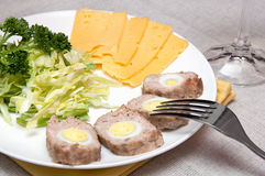 Meat roll with quail eggs. Cheese, cabbage salad on white plate with fork and knife Stock Photos