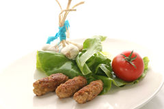 Meat rolls on a plate with salad. And tomato Royalty Free Stock Images