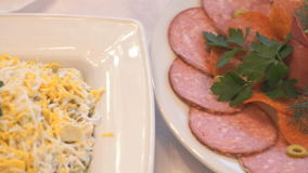 Meat salad, sliced pieces of salami on the saucers stock footage