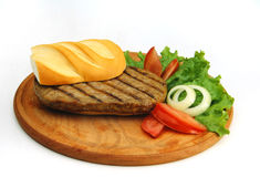 Meat sandwich. Tasty meat sandwich with tomatoes, lettuce and onions in a wood plate royalty free stock photography