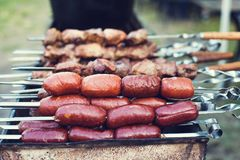 Meat and sausages on fire. Meat and sausages are cooked on the grill during a picnic in nature. cooking meat on fire Royalty Free Stock Images