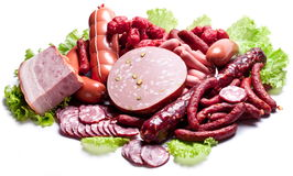Meat and sausages on lettuce leaves. Stock Photos