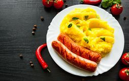 Meat sausages with mashed potatoes in a plate on dark wooden background Stock Photography