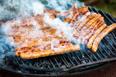 Meat sausages roasted on the grill Stock Photo