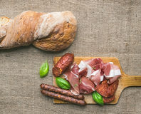 Meat selection / wine set on a rustic wood board over a rough sa Royalty Free Stock Photography