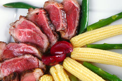 Meat served on white with corns Stock Image