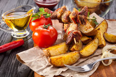 Meat skewer with herbs With onions, baked potatoes, tomatoes and greens Royalty Free Stock Images