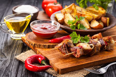 Meat skewer with herbs With onions, baked potatoes, tomatoes and greens Royalty Free Stock Photography