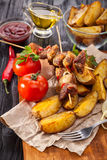 Meat skewer with herbs With onions, baked potatoes, tomatoes and greens Royalty Free Stock Photos