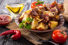 Meat skewer with herbs With onions, baked potatoes, tomatoes and greens Royalty Free Stock Image
