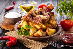 Meat skewer with herbs With onions, baked potatoes, tomatoes and greens Stock Image