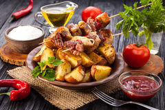 Meat skewer with herbs With onions, baked potatoes, tomatoes and greens Royalty Free Stock Photo