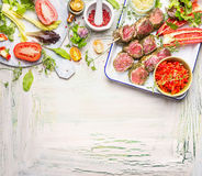 Meat skewers with fresh herbs, spices and vegetables ingredients for grill or cooking. Preparation on light wooden background, top Stock Photos