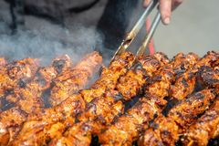 Meat on skewers fried on the grill in the open air, visible hand. S of the cook stock photography
