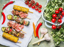 Meat Skewers for grill with vegetables , corn ears and condiment, preparation on rustic background Royalty Free Stock Image
