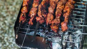 Meat on skewers grilled over the glowing. Tasty roasted grill meat with crust. Close up of pork meat prepared on fire stock video footage