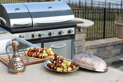 Skewers and Outdoor Kitchen. Meat skewers with vegetables at the outdoor kitchen on the concrete counter top. Skewers are in the traditional and authentic Stock Images