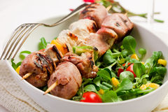 Meat Skewers on white table. Delicious broiled meat skewers on white table stock photography