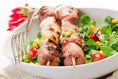 Meat Skewers on white table. Delicious broiled meat skewers on white table royalty free stock image
