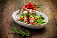 Meat Skewers on wooden table. Delicious broiled meat skewers on wooden table with salad stock photography