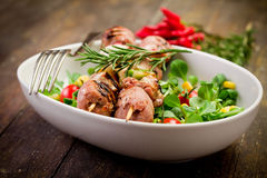 Meat Skewers on wooden table. Delicious broiled meat skewers on wooden table with salad royalty free stock photography