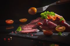 Meat sliced with greens on a black background. The meat sliced with greens on a black background Royalty Free Stock Image
