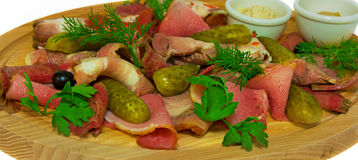 Meat slices with cucumber. on the wooden substrate. on  background. Meat slices with cucumber and green, on the wooden substrate. on  background Royalty Free Stock Photos