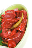 Meat slices over ceramic bowls ready to prepare with red peppers Stock Photography