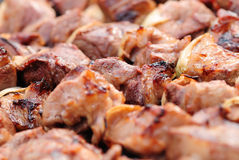 Meat slices prepare on fire. Juicy slices of meat with sauce prepare on fire royalty free stock photos