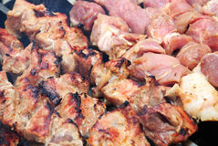 Meat slices prepare on fire. Juicy slices of meat with sauce prepare on fire royalty free stock image