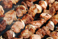 Meat slices prepare on fire. Juicy slices of meat with sauce prepare on fire stock image