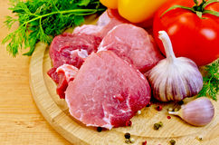 Meat slices on a wooden board with vegetables Royalty Free Stock Photo