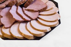 Meat slicing of ham and sausage in a black plate on white background stock photo