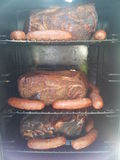 Meat in a smoker Stock Images