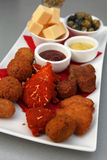 Meat snacks. Different kinds of deep fried meat snacks accompanied by sauces, cheese and olives Stock Images