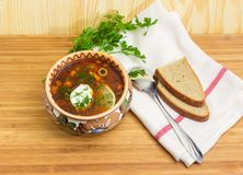 Bowl of meat solyanka, spoon, bread on wooden surface. Meat solyanka in ceramic bowl, spoon, slices od brown bread and greens on a napkin on a bamboo wooden stock photo