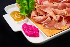 Meat and sowbelly set. pub, restaurant, bar food concept. meat appetizers set with meat, sowbelly, tomatoes cherry, souses and. Fresh greens royalty free stock photography
