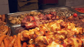 Meat Specialities Trays. Lots of grilled meat products, arranged on trays, on a night outdoor swedish  buffet stock video footage