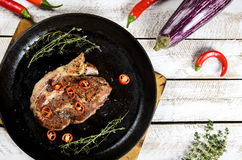 Meat with spices in a pan, rosemary, and hot chili peppers on a white wooden table background Stock Image