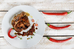 Meat with spices in a pan, rosemary, and hot chili peppers on a white wooden table background Stock Photos