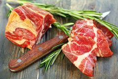 Meat and sprigs rosemary closeup. Royalty Free Stock Photo